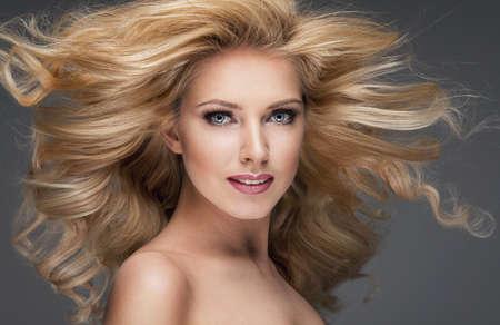 mujer rubia desnuda: Sensual hermosa mujer rubia posando con el pelo largo y rizado.