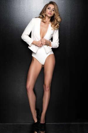 skinny: Sexy mujer rubia delgada que presenta en estudio el uso de chaqueta de moda y pantalones Foto de archivo