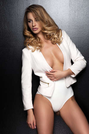 vouge: Sexy slim blonde woman posing in studio wearing fashionable jacket and pants Stock Photo