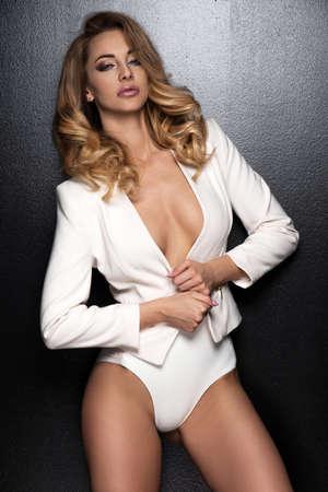 slim: Sexy slim blonde woman posing in studio wearing fashionable jacket and pants Stock Photo