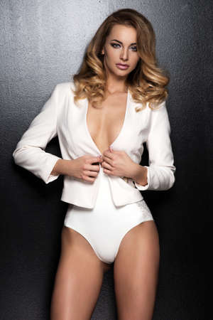 jackets: Sexy slim blonde woman posing in studio wearing fashionable jacket and pants Stock Photo