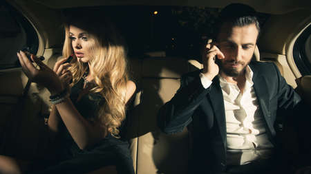 couple in the car. Young woman applying lipstick and man using cell phone in car.