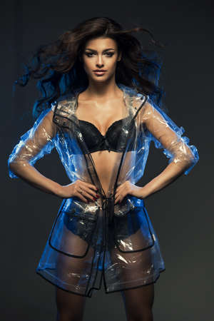 Sexy woman only in lingerie with transparent coat highlighted in blue