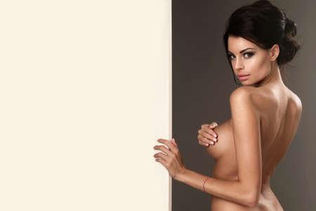 topless brunette: Beautiful brunette woman with white blackboard Stock Photo