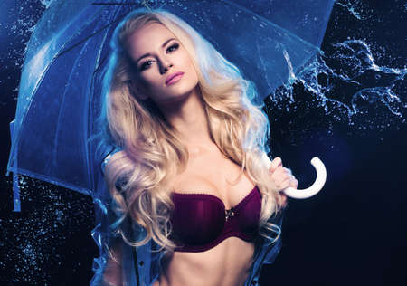 blue lingerie: Young sexy woman with transparent umbrella. Stock Photo