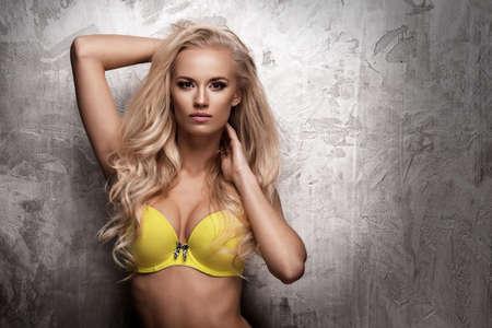 mujeres eroticas: Sensual hermosa mujer rubia posando en ropa interior amarilla en fondo concreto Foto de archivo