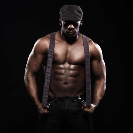 naked african: Portrait of an athletic african american man topless. Only in suspenders and cap