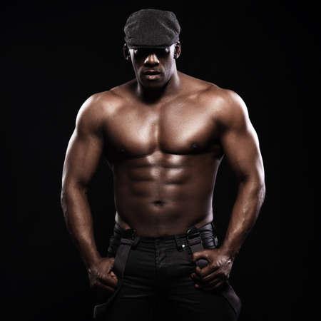 seins nus: Portrait d'un homme afro-américain torse nu athlétique. Seulement en bretelles et chapeau Banque d'images