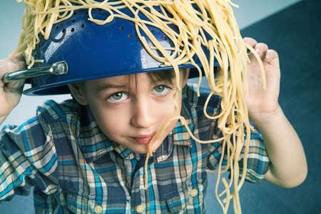 Surprised boy with pasta on the head Standard-Bild