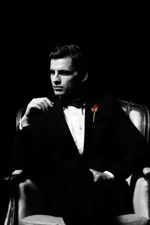Portrait of man who sitting on chair, godfather-like character. photo