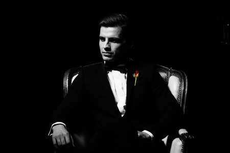 Portrait of man who sitting on chair, godfather-like character. Stockfoto