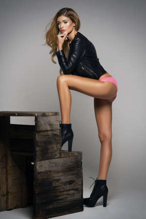 seductress: Sexy blonde woman in leather jacket Stock Photo