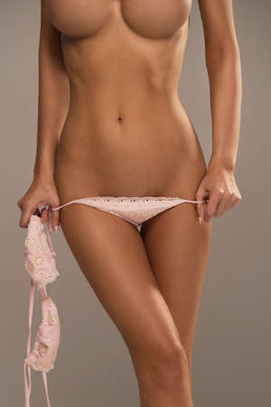 breasts: Half-length portrait of sexy beautiful woman with great figure wearing pink swimwear showing Stock Photo
