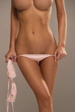 pechos: La mitad de longitud retrato de la mujer hermosa atractiva con gran figura que muestra el uso de trajes de baño de color rosa Foto de archivo