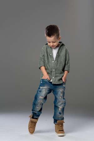 cute guy: Fashion boy looking down on grey background
