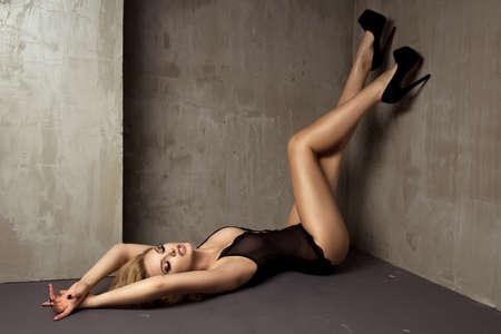 Sexy blonde vrouw in lingerie liggend op de vloer