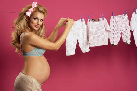 woman pregnant: Pregnant woman posing next to baby clothes over pink background