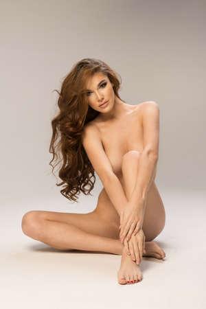 nudo integrale: Giovane e bella donna bruna nuda seduta su sfondo