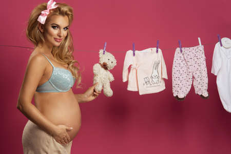 woman clothes: Pregnant woman posing next to baby clothes over pink background