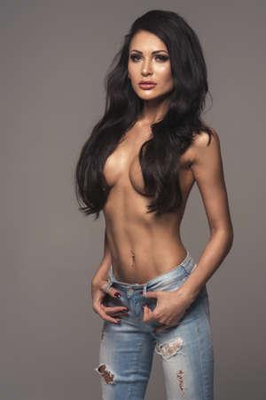 mujeres eroticas: Mujer atractiva atractiva morena posando sólo con jeans en el estudio