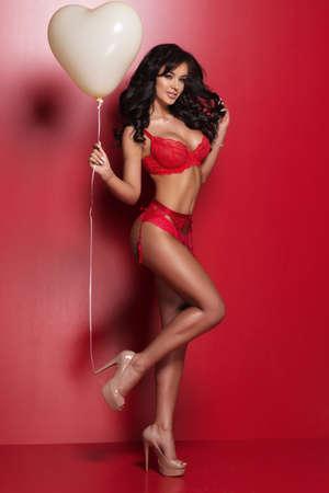 Mujer atractiva morena valentín llevar lencería de color rojo con el globo del corazón. Día de San Valentín. Foto de archivo