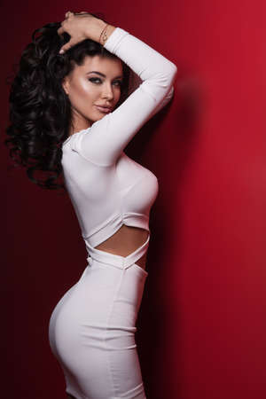 labios sexy: Beautiful model in white dress posing on red background