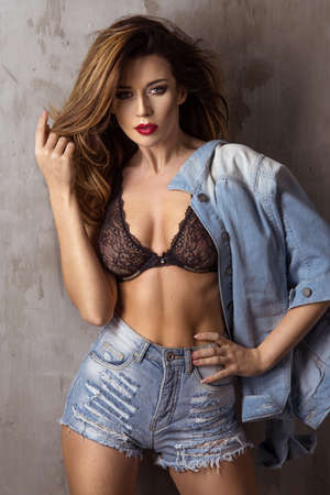 belle brune: La mode brune belle femme posant en studio portait un jean court et veste, regardant la caméra.