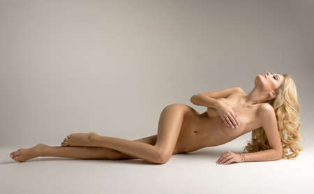 Beautiful young naked blonde woman sitting over the background Stock Photo