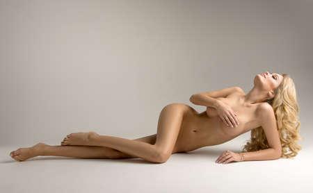 Schöne junge nackte blonde Frau sitzt auf dem Hintergrund Standard-Bild - 60746761