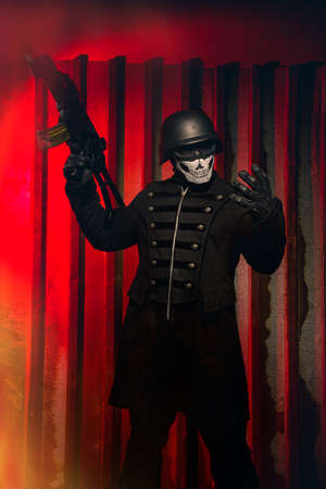 tremor: Danger man in mask with rifle over red background