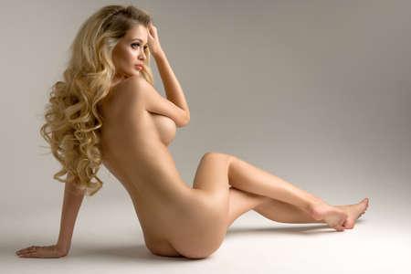 Schöne junge nackte blonde Frau sitzt auf dem Hintergrund Standard-Bild - 60746766