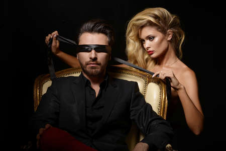 Sexy Paar Love, Blindfold man in pak met sexy blonde vrouw Stockfoto