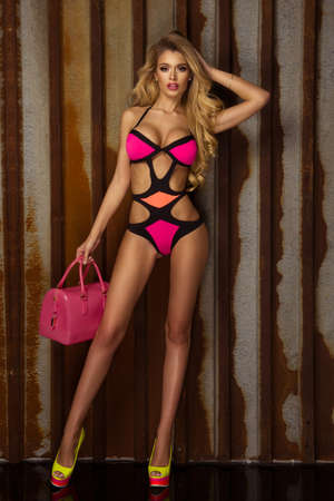 Fashionable photo of attractive young blonde beauty posing in pink swimwear, looking at camera. Stock Photo