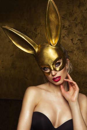 긴 귀와 카니발 골드 토끼 마스크에 아름 다운 금발의 젊은 여자 스톡 콘텐츠