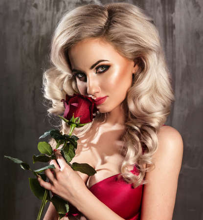Close-up portrait of beautiful blonde woman with red rose photo