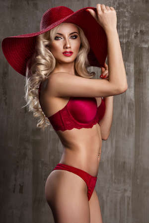 Beautiful young woman wearing summer red hat with large brim photo