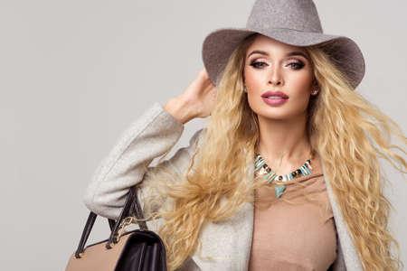 Fashion blonde model v pěkné oblečení pózuje ve studiu. Nosit kabát, klobouk a kabelku, roztrhl