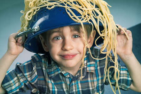 food dish: Surprised boy with pasta on the head Stock Photo