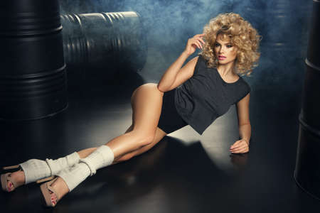 prowess: Young modern dancer with blonde curly hair in dark room Stock Photo