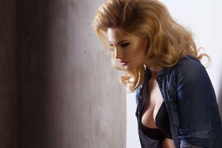 fille sexy: Fashionable blonde beautiful woman posing in studio wearing jeans