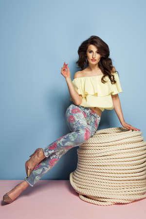 mujeres fashion: chica de moda morena llevaba ropa en colores pastel cerca de las cuerdas