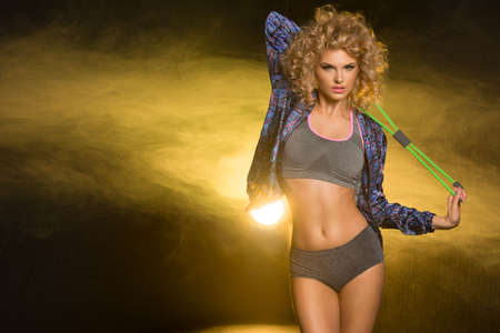 prowess: Young modern sport woman with blonde curly hair in dark room