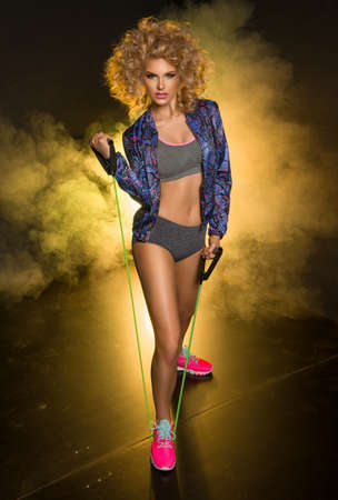 Young modern sport woman with blonde curly hair in dark room