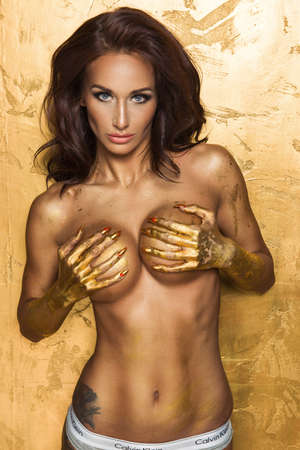 waxy: Sexy woman over gold background with metal gold hand