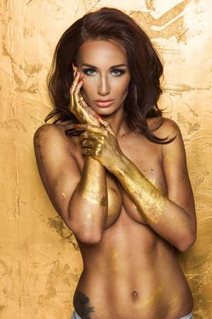 uñas pintadas: La mujer atractiva sobre fondo de oro con la mano metal oro Foto de archivo