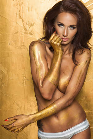 Sexy woman over gold background with metal gold hand