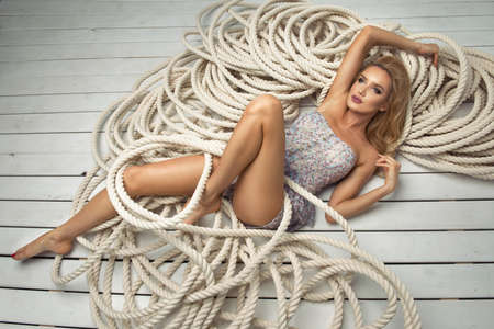 Sexy blond woman lying on white rope Stock Photo