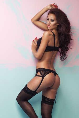 piernas con tacones: Mujer joven de fascinación hermosa en ropa interior atractiva sobre el fondo en colores pastel