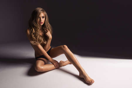 naked woman: Beautiful young naked blonde woman sitting over the background Stock Photo