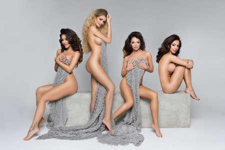 topless: Quatre belles femmes sur bloc de béton Banque d'images